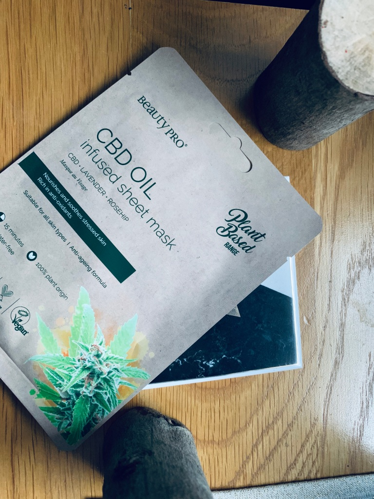 A CBD oil infused sheet mask in it's packet displayed on a wooden table on a marble cup place mat.