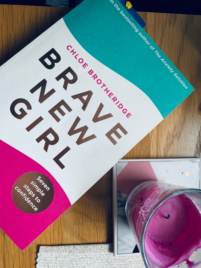 """A flatlay of a book called """"Brave new girl"""" by Chloe Brotheridge. Laying on a wooden table."""