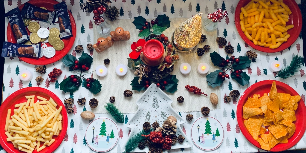 A festive host set up on a table including; four plates filled with crisps or chocolate coins/snowmen, then decorated with gingerbread salt and pepper shakers, a centre piece with a candle, a mini lit up gold tree, ice skating scenes cup place mats, a white tree shaped plate with tree paintings on it. Decorated with pine cones, holly and acorns around the table.