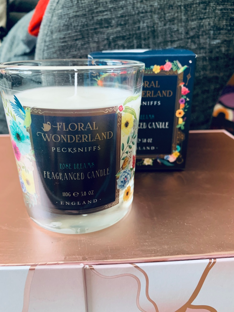"""A """"floral wonderland"""" small candle next to its beautifully decorated box. Has the feeling of the flowers and Alice in wonderland theme."""