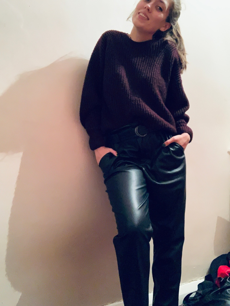 A woman wearing a burgundy jumper and leather trousers!