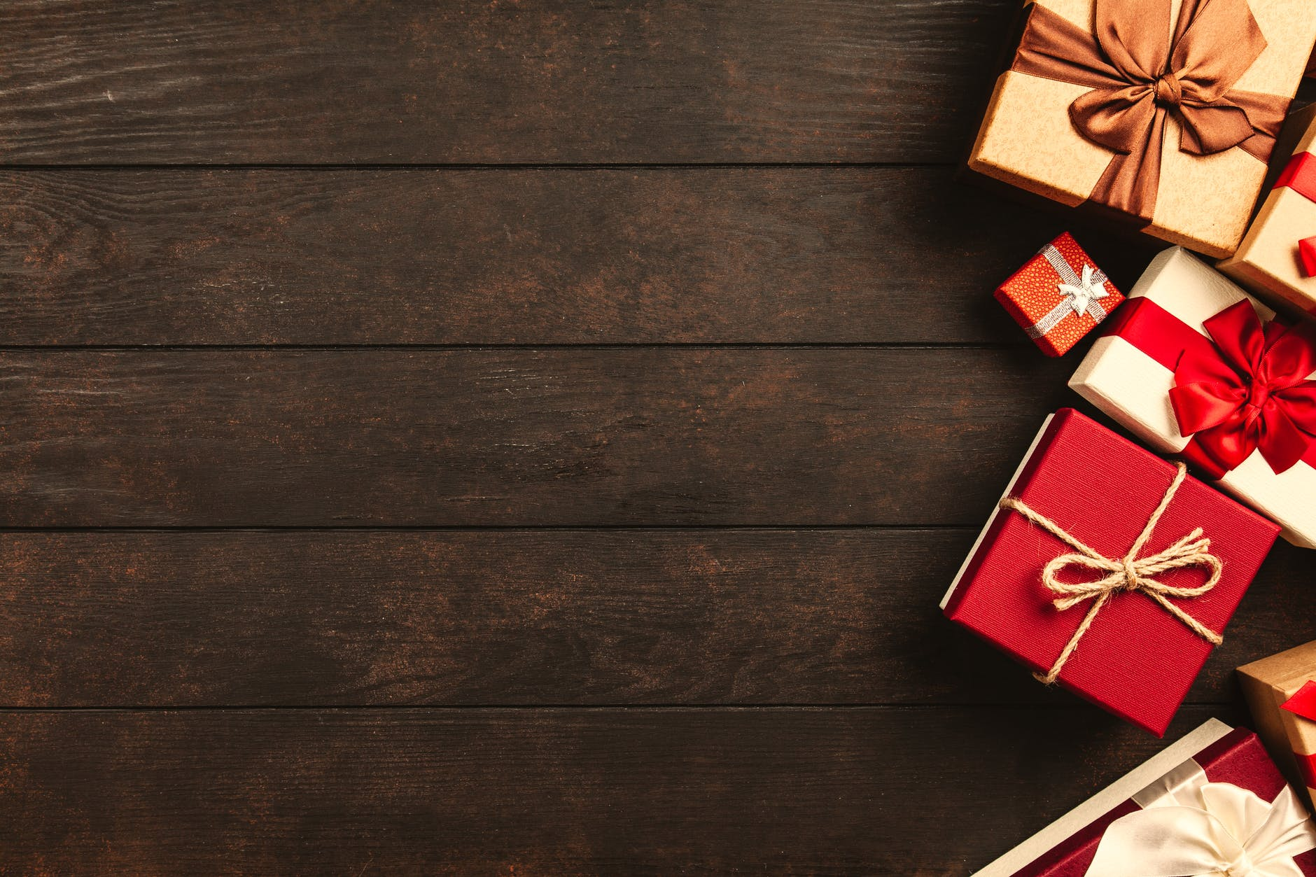 A dark wooden floorboard with a selection of gold and red presents on the right hand side.