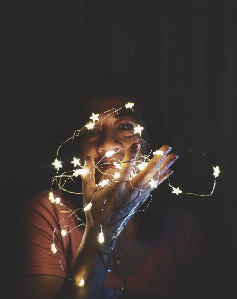 Someone in the dark whilst holding up starry fairy lights so you just see their face and hands slightly