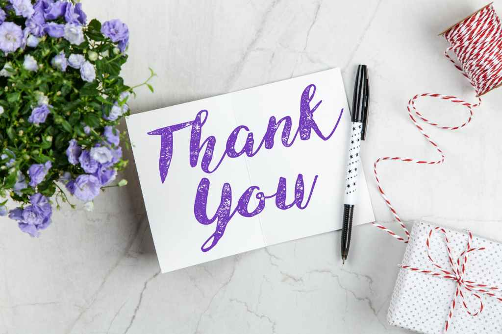 """A pad with """"thank you"""" on it in purple writing and a pen, next to a present with string and blue flowers."""