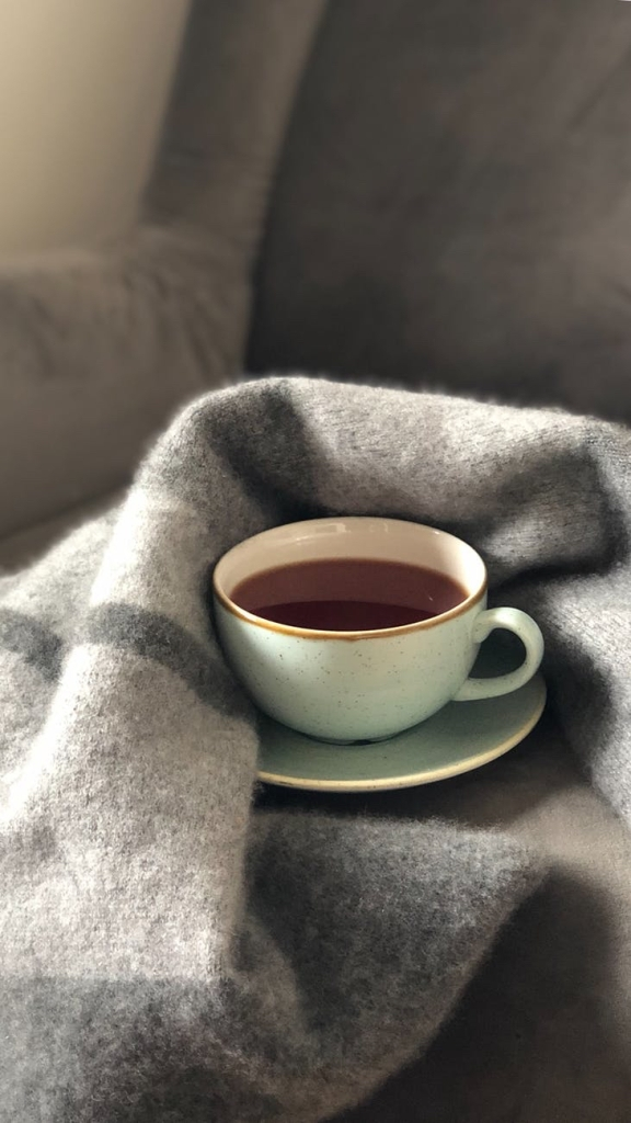 A cup of tea wrapped up in a blanket on the sofa