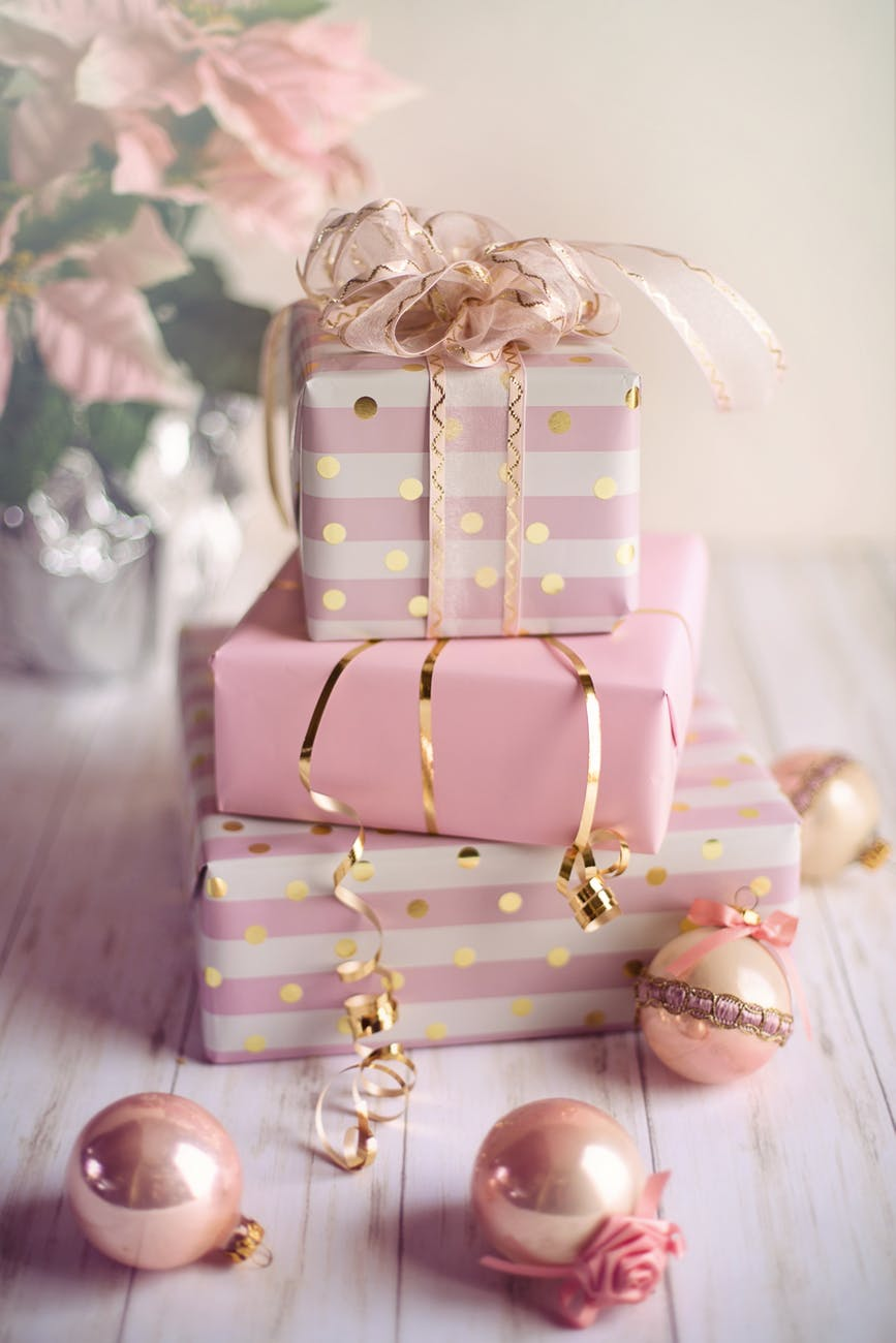 A selection of pink wrapped up presents piled on top of each other, with some baubles in front of them.