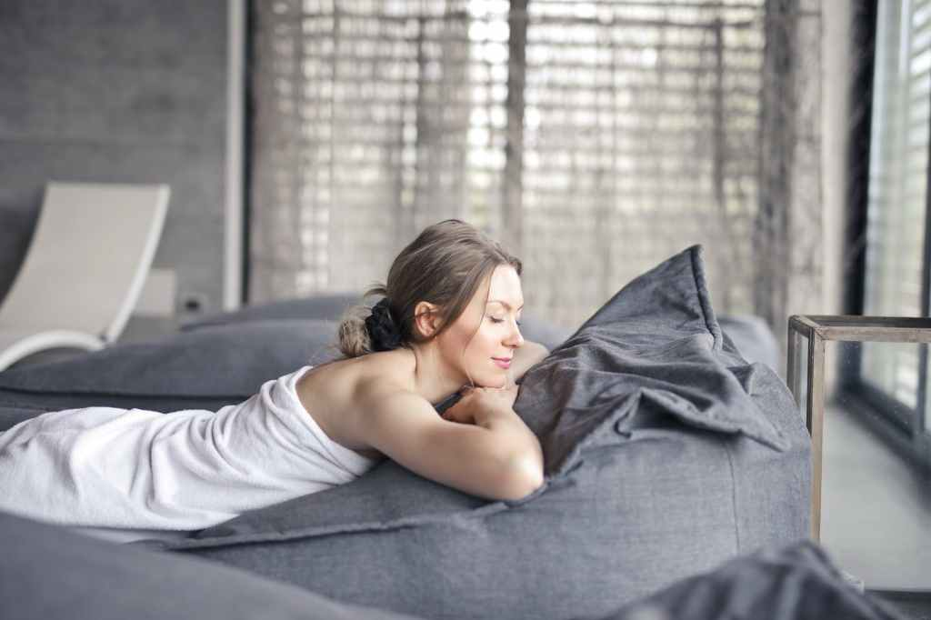 A woman laying down on a bed in a towel with her eyes closed, relaxed and practicing self-care.