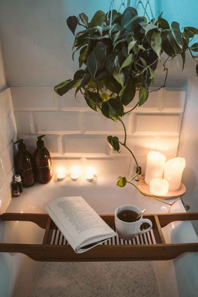 A filled up bath with a tray that has a hot drink and a book, with candles in the corner and around the edge.