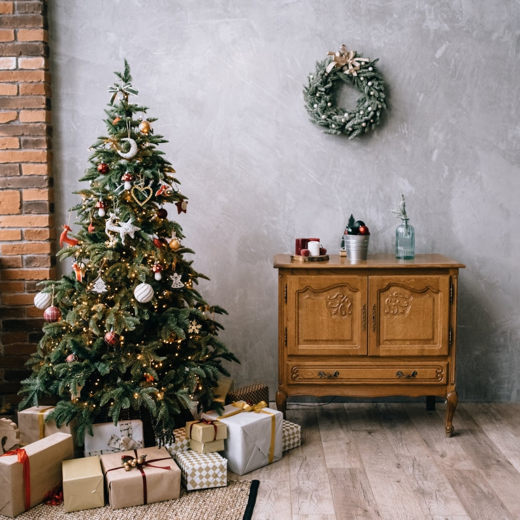 A decorated Christmas tree with presents underneath, against a grey wall and next to a brown chest of drawers.