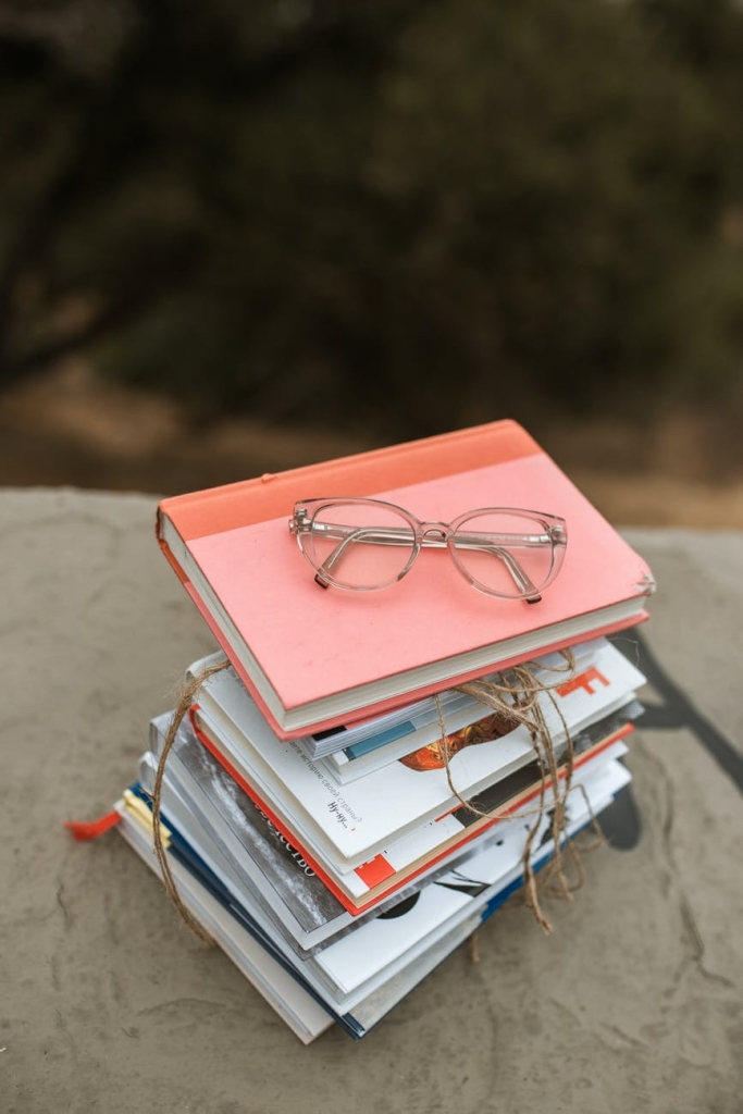 A stack of different books with a pair of glasses on the top!