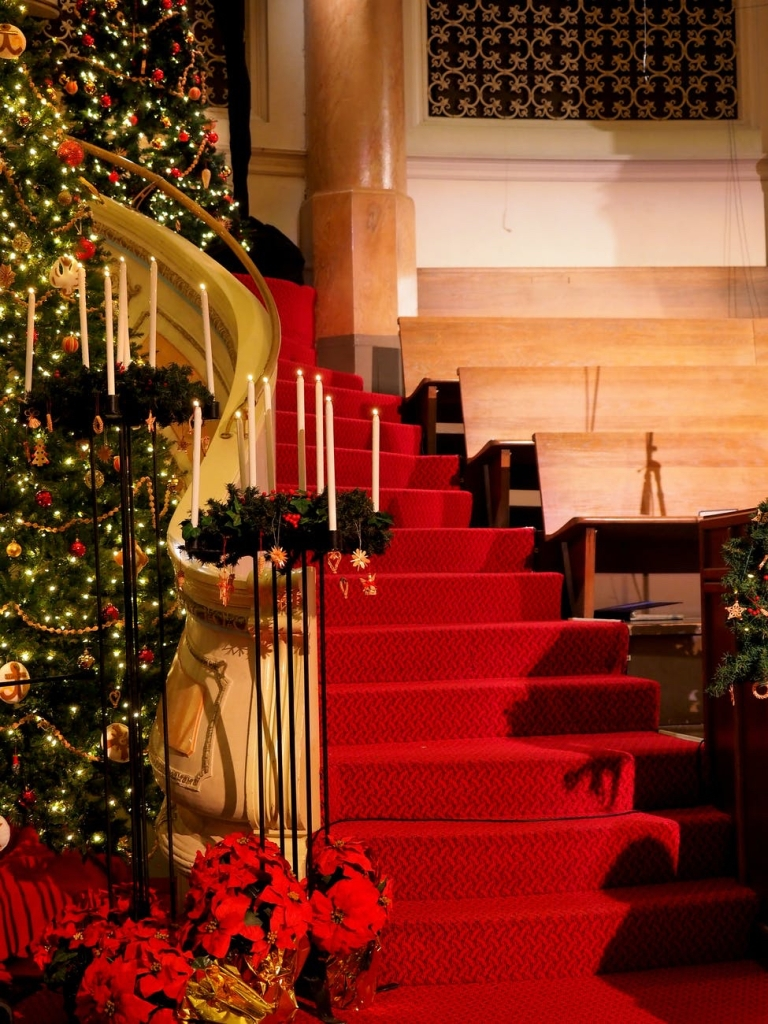 A stair case surrounded by candles and Christmas decorations and lights
