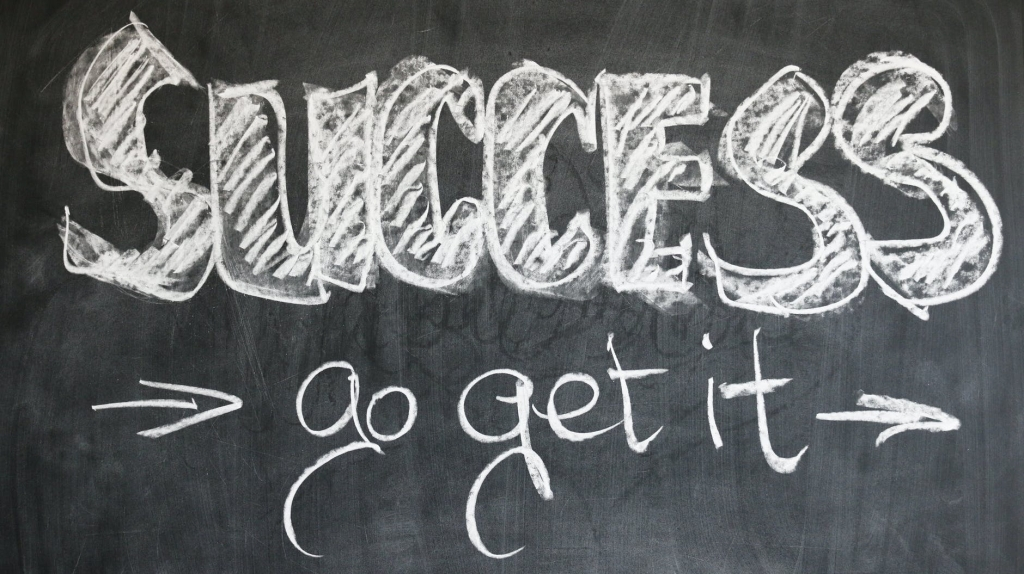 "A black board with ""success go get it"" written on it  with arrows pointing to the ""go get it"" either side"