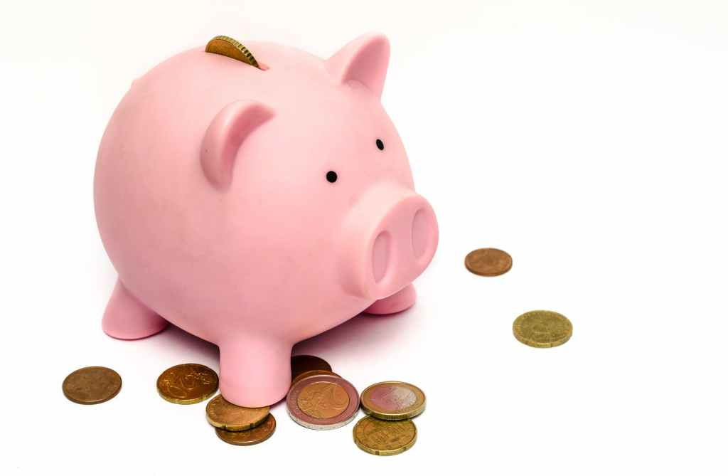 A pink piggy bank with a collection of coins scattered around it and one coin sticking out of the top.