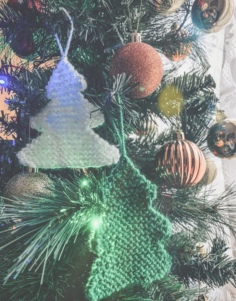 Tiny knitted white and green Christmas trees hanging on a real Christmas tree as a close up