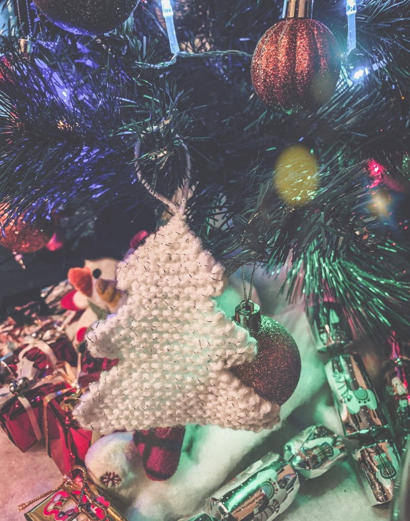 A small knitted  white Christmas tree hanging on an actual Christmas tree