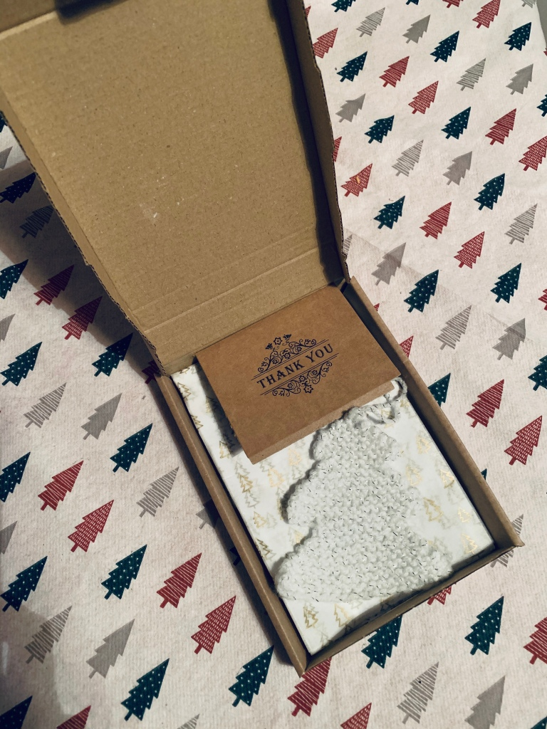 A small cardboard box filled with tree tissue paper and a small knitted white tree with a thank you card. From a small business.