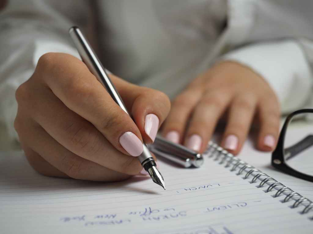 Someone's hands holding an ink pen and writing on a lined notepad.
