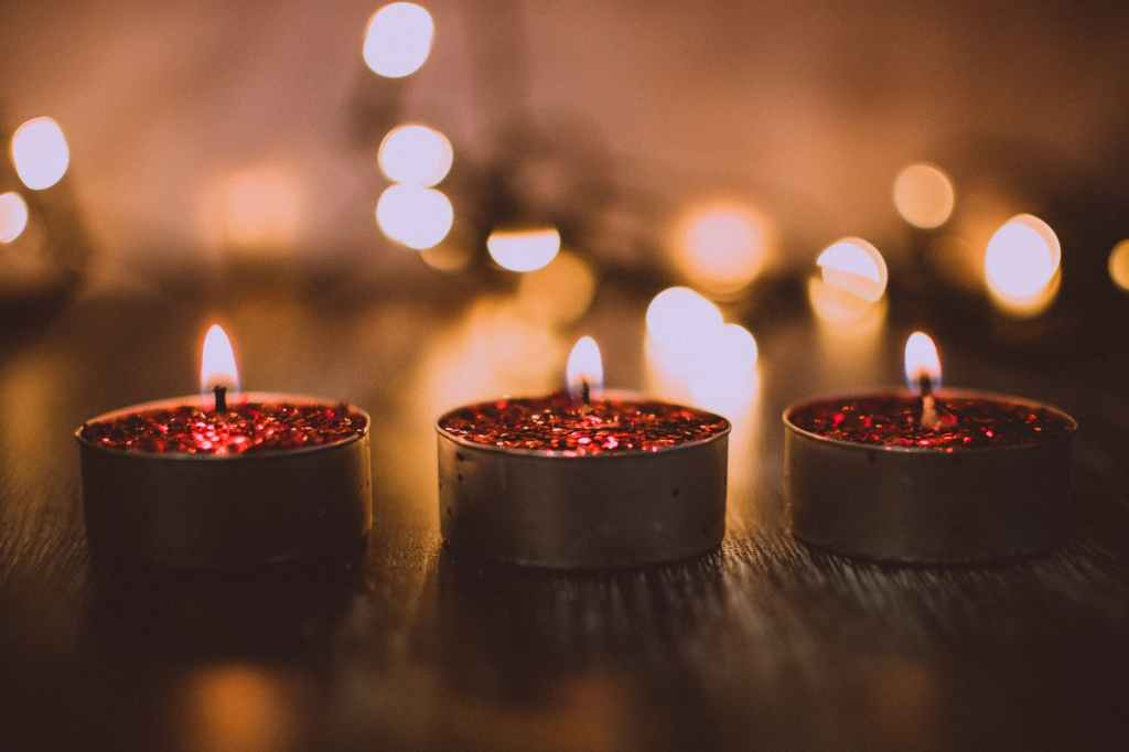 Three sparkly red small candles in a line all lit up, with a blurry light background.