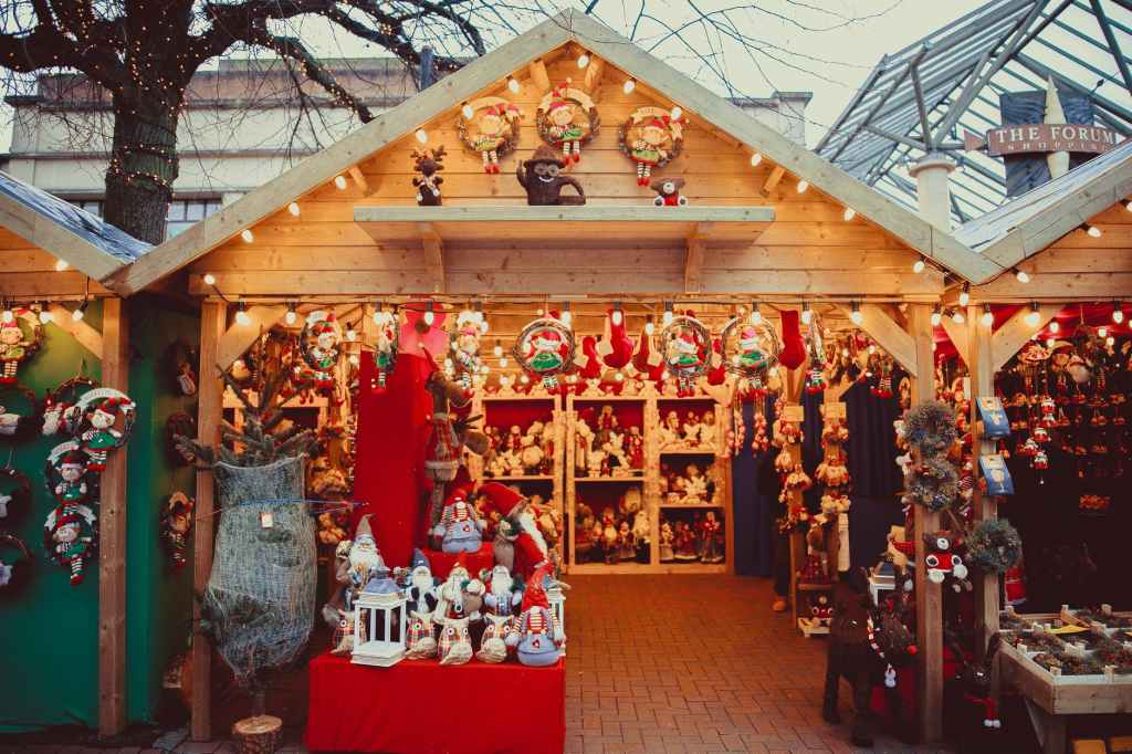 A stall at a Christmas market filled with garlands, statues and other decorations with a festive theme.