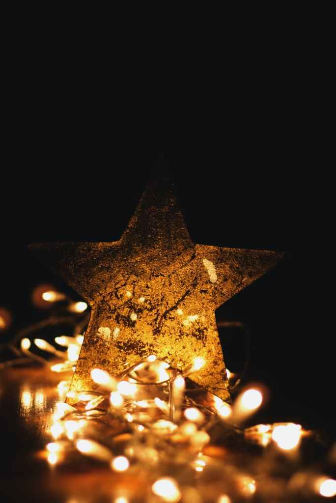 A light up Christmas star with fairy lights all lit up underneath it.