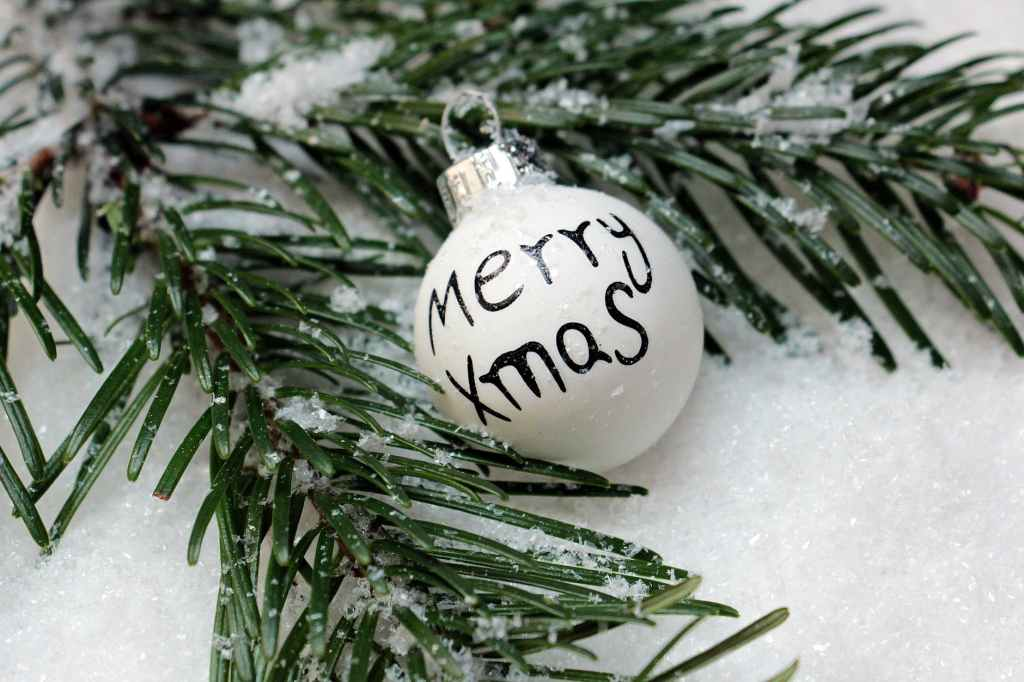 """A selection of white snow, with some Christmas tree branches laying in it and a white Christmas Bauble with """"Merry Xmas"""" on it in black writing."""