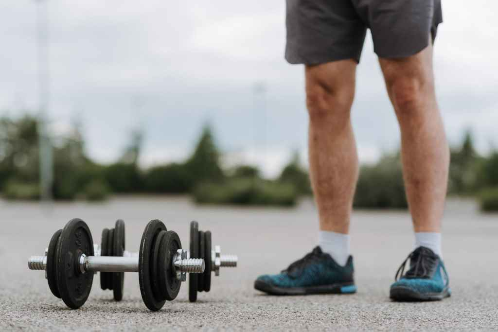 A man standing next to some weights a view of he's legs, outside in the street.