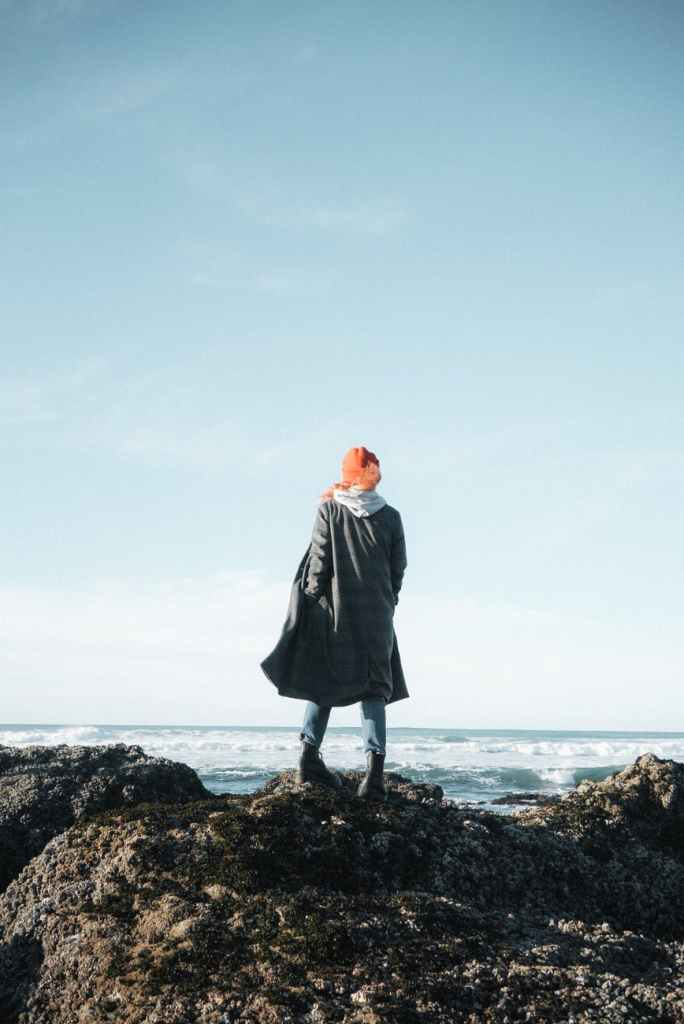 A woman standing on a rock looking out into the sea wearing a long coat with a hoodie underneath, and a red hat.