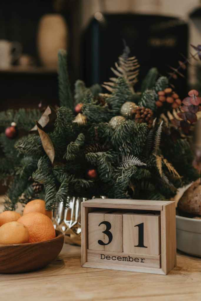 """A christmas tree bowl with a wooden sign that says """"31 December"""" on it that you can change, next to a bowl of oranges in front of the Christmas tree bowl."""
