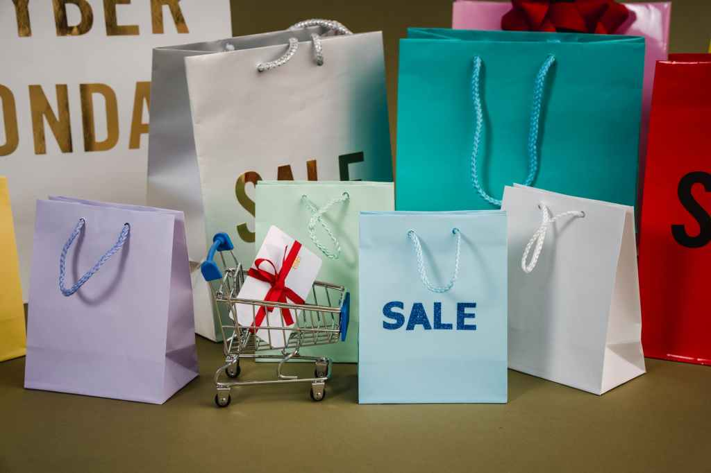 """A selection of big and small gift bags some with the words """"sale"""" on the front of them, and a small shopping trolley with a gift card wrapped in a red bow in it."""
