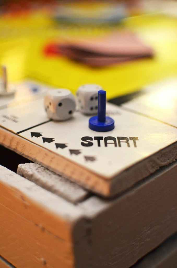 """A board game zoomed in at the """"start"""" position with a blue character and two dice."""