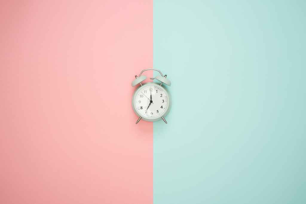 A pink and blue background with a small clock in the middle of the photo.