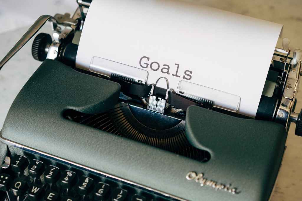 """A silver/grey type writer with """"goals"""" written on the parchment paper in the type writer."""