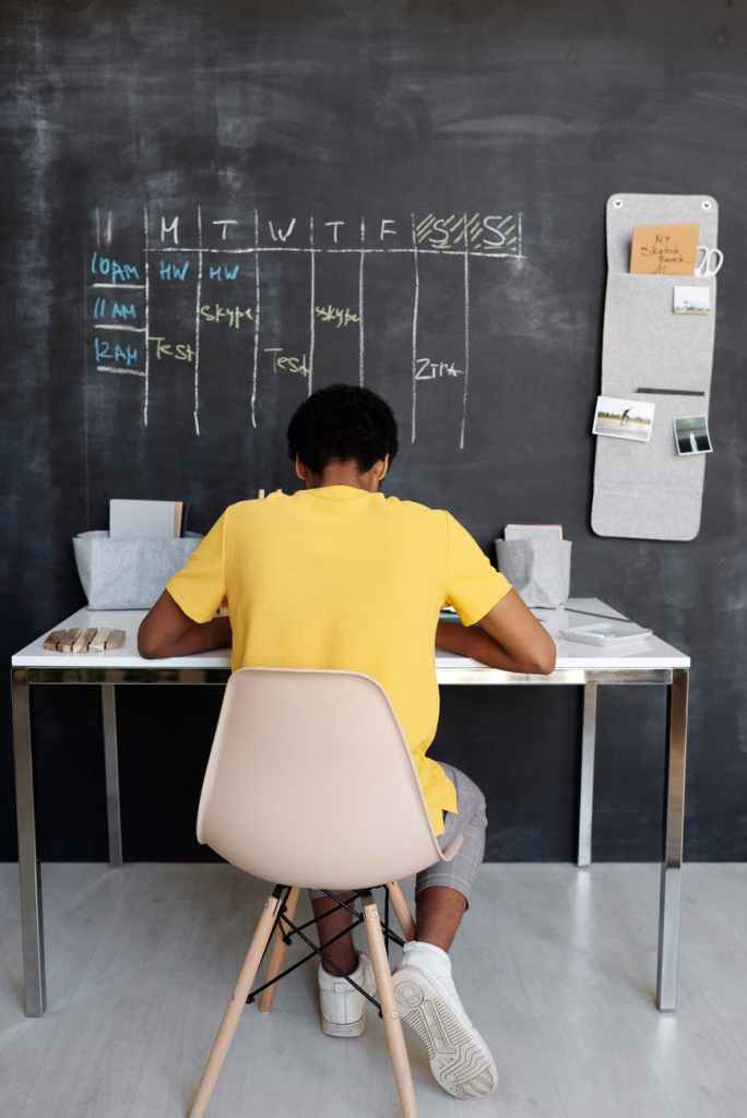 """A woman sitting facing a huge wall blackboard, with """"Monday to Sunday"""" on the blackboard written in chalk whilst the woman is working on the desk area."""