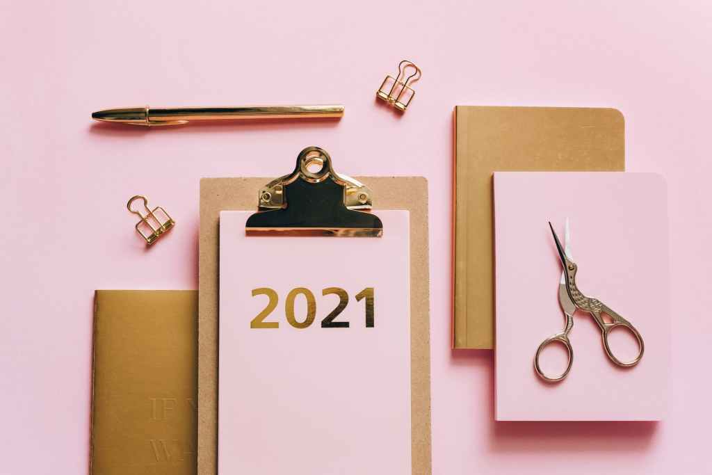 """A pink background, with a brown clipboard with """"2021"""" on pink paper in gold writing attached to the clipboard. next to brown notebooks and one pink notebook with some scissors on top of them."""