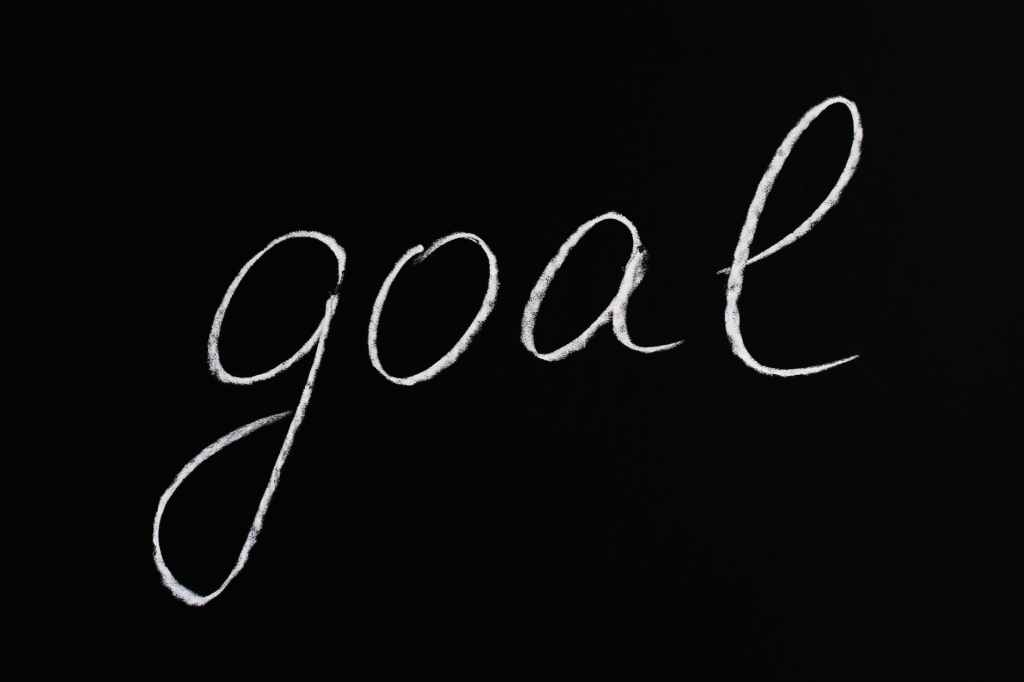 """A black background with the word """"goal"""" written on it in a white chalk."""