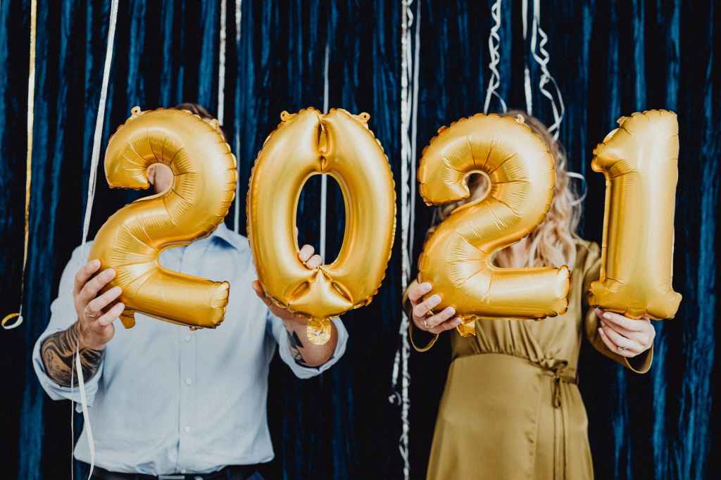 """A man and a woman holding up golden """"2021"""" balloons covering their faces."""